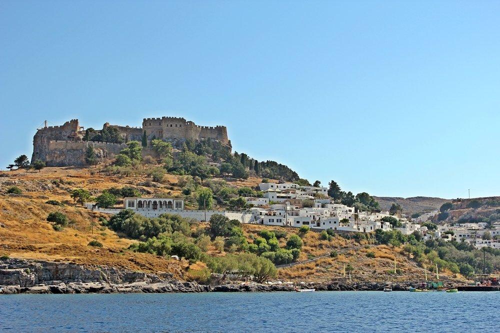 Blick vom Meer aus auf die weißen Häuser von Lindos die unterhalb der Akropolis liegen. Ausflugstipp für Rhodos