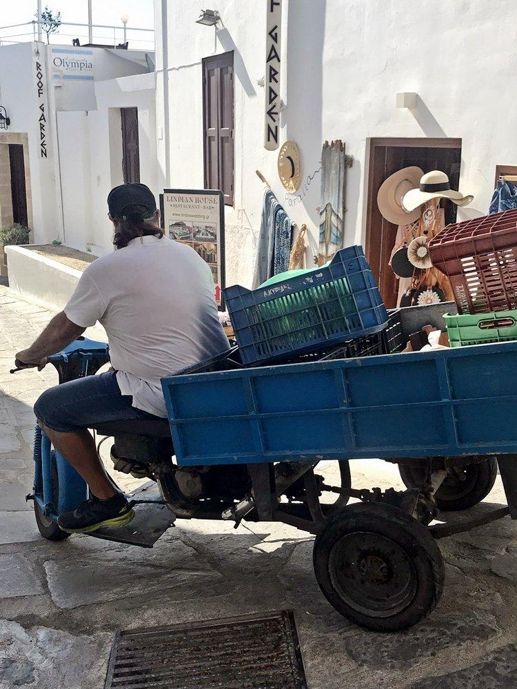Zu einem Transportfahrzeug umgebauter Roller der durch die engen Gassen Lindos fährt. Ausflugstipp für Rhodos