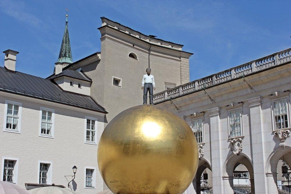 Gesamtkunstwerk Sphaera. Hier der Mann auf der goldenen Kugel. Das Kunstwerk befindet sich auf dem Kapitelplatz Salzburgs.