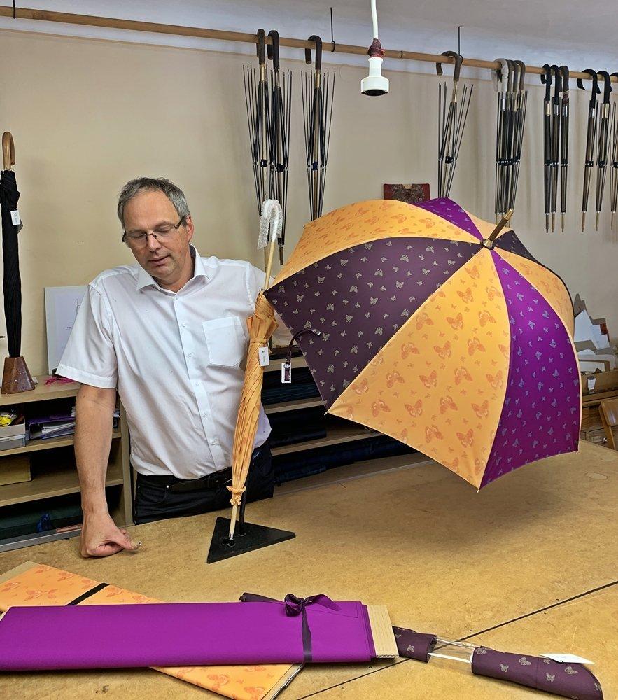 Herr Kirchtag präsentiert einen handgefertigten Regenschirm