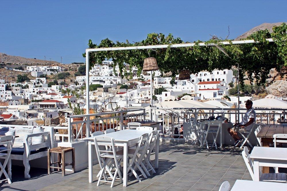 Blick von weiß möblierter Rooftop-Bar auf Lindos weißen Häuser, Ausflugstipp für Rhodos