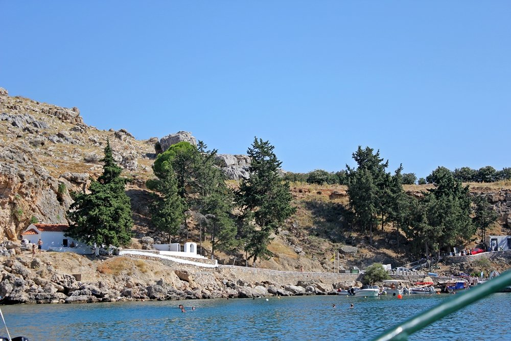 Blick vom Boot auf die weiße Kapelle in der St. Pauls Bay in Lindos, Ausflugstipp für Rhodos