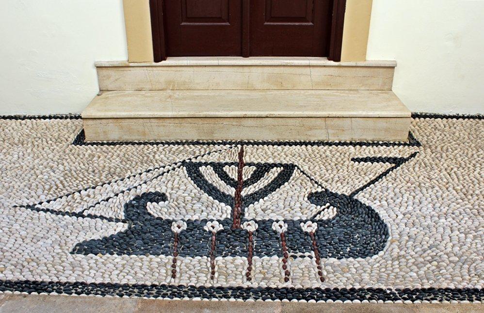 Ein Mosaik aus Steinen, dass ein Schiff darstellt.