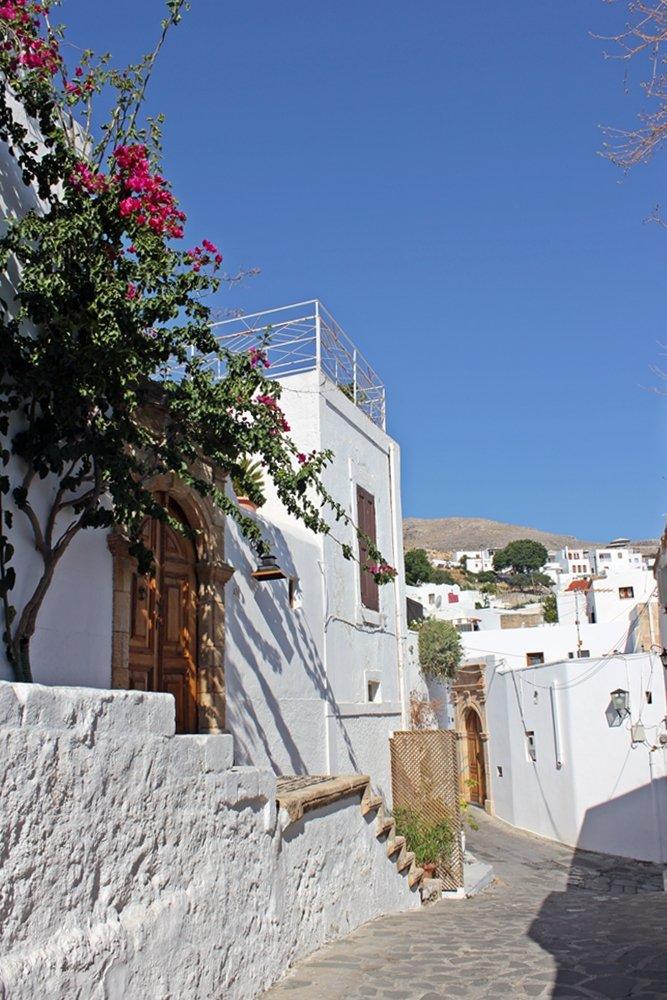 Eine wunderschöne Gasse mit weißgetünchten Häusern und blühenden Blumen. Ausflugstipp für Rhodos