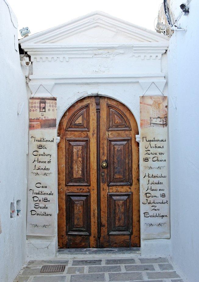 Eine braune Holztür mit Schrift auf einer weißen Wand in Lindos